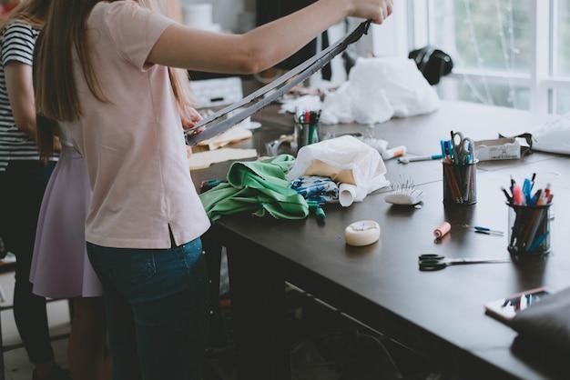 Портной в процессе работы в своей мастерской. швейные принадлежности на столе.
