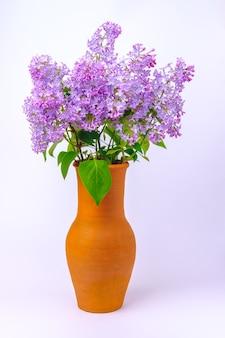 咲くライラックと緑の葉の花束と背の高い茶色の陶器の花瓶は、柔らかい影を落とすテーブルの上に立っています