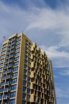 窓のある建設中の高層ビル。住宅用不動産。モーゲージ