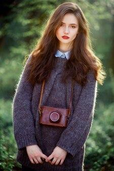 Высокая худенькая девушка с длинными темными волосами в теплом оверсайз шерстяном свитере со старинным пленочным фотоаппаратом в кожаном футляре на шее стоит на фоне зеленого леса на закате.