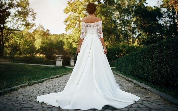 Загорелая девушка-невеста в шикарном белом свадебном платье с открытыми плечами стоит повернувшись спиной в парке на аллее