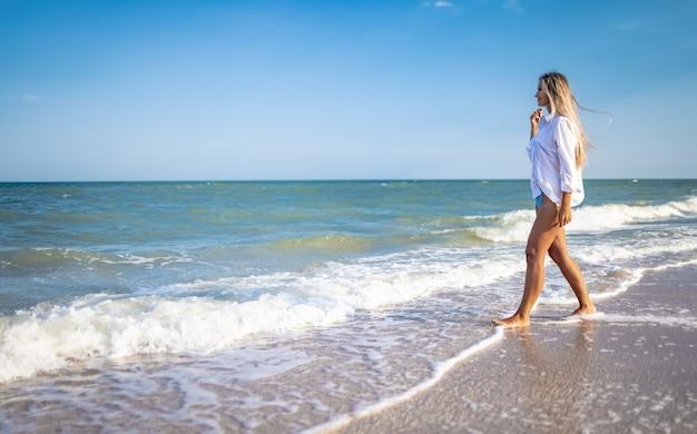 Загорелая девушка в синем купальнике и легкой рубашке наслаждается летом на берегу моря.