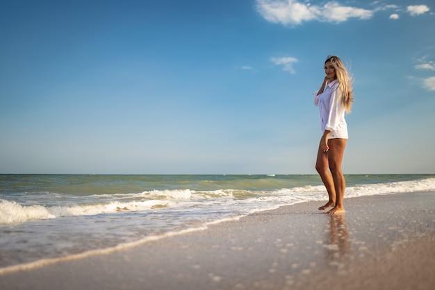 青い水着と薄手のシャツを着た日焼けした女の子が海辺で夏を楽しんでいます