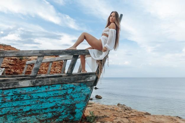 Загорелая девушка в сексуальном белом платье сидит на носу разрушенного корабля на пляже