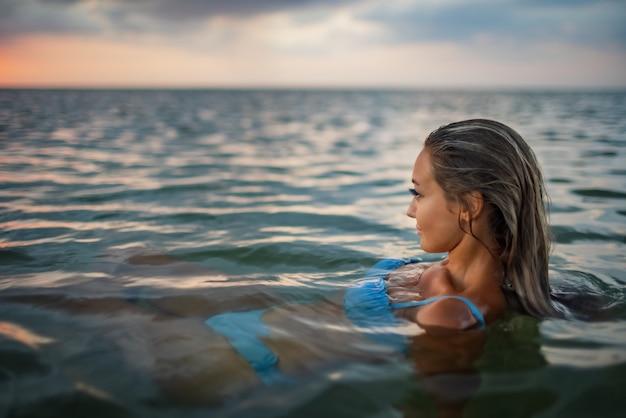 젖은 금발 머리에 표정이 풍부한 그을린 소녀가 석양을 배경으로 투명한 물이 있는 깨끗한 강어귀에 앉아 알 수 없는 거리를 바라보고 있습니다.