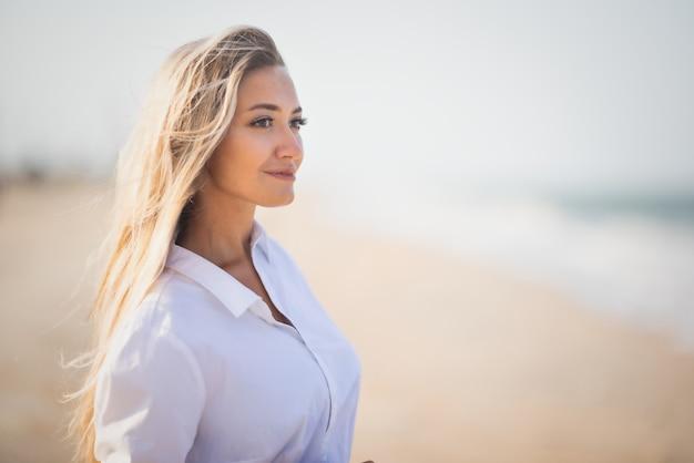 青みがかった水着と白い薄手のシャツを着た日焼けしたほっそりした女の子は、荒れ狂う青い海の海岸で暖かい晴れた夏を楽しんでいます