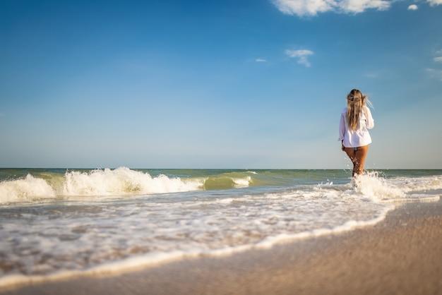 푸른빛이 도는 수영복과 흰색 가벼운 셔츠를 입은 검게 그을린 날씬한 소녀가 성난 푸른 바다의 해안에서 따뜻하고 화창한 여름을 즐깁니다.