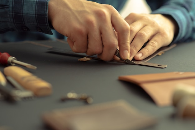 Дубильщик на черном столе делает аксессуар из натуральной коричневой кожи. бизнес-концепция кожи.