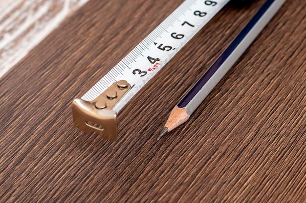 暗い板に巻尺とシンプルな鉛筆が横たわっている