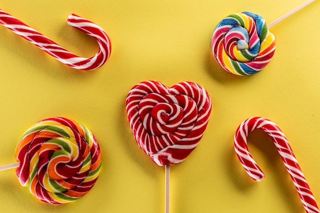 Вкусный набор сладких конфет, таких как леденцы на палочке, с цветом радуги и желтым фоном.