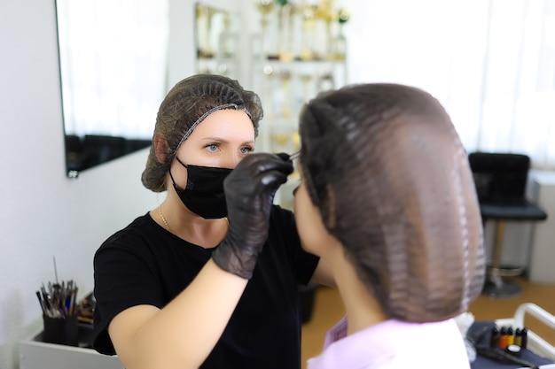 Художник-татуировщик в черной маске и черном защитном колпаке стоит перед клиенткой, рисуя эскизы будущих бровей.