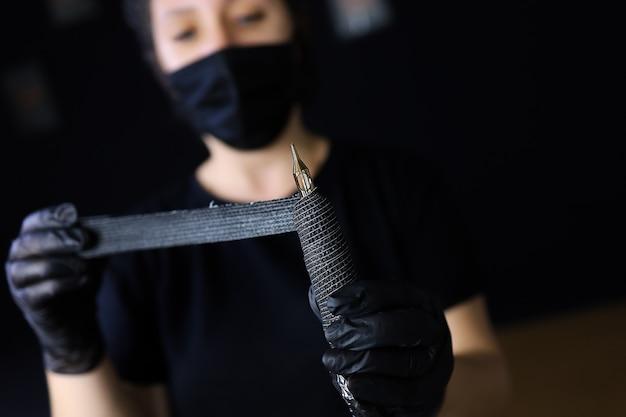 黒い手袋をはめたタトゥーアーティストは、彼女の前にタトゥーマシンを持ち、ストレッチテープで包んで固定します
