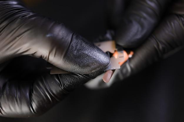 Художник-татуировщик в черных перчатках точит карандаш лезвием до отметки.