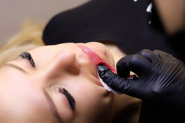 黒い手袋をしたタトゥーアーティストが、モデルの唇からタトゥー用の余分な赤い顔料を拭き取ります