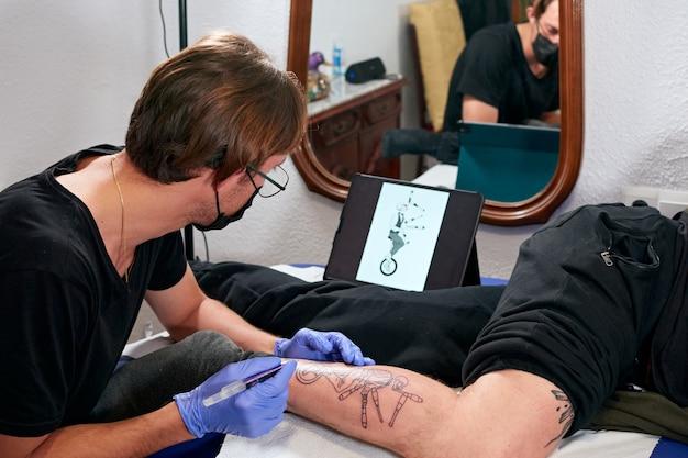태블릿을보고 스튜디오에서 남성의 다리에 문신을하는 파란색 장갑의 문신 예술가