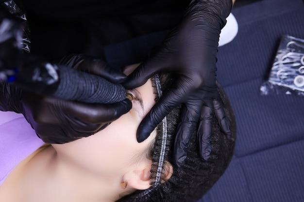 Художник-татуировщик в черных перчатках выполняет перманентный макияж бровей. одна рука держит голову клиента, другая работает с тату-машинкой