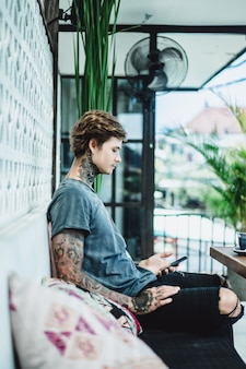 A tattooed man in a cafe uses a smartphone, drinks coffee