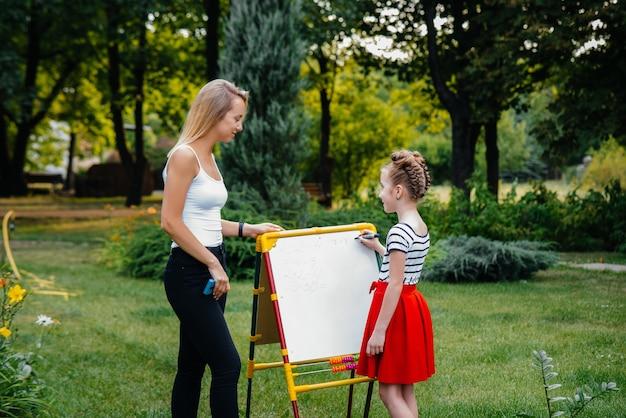 교사는 야외 공원에서 어린이 수업을 가르칩니다.