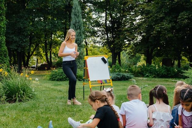 교사가 야외 공원에서 아이들을 가르치고 있습니다.
