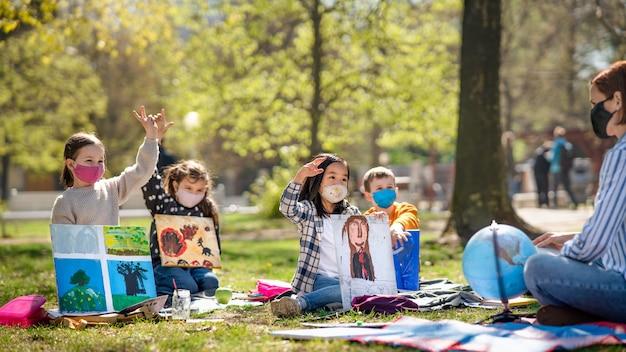 都市公園の屋外に座っている小さな子供を持つ教師