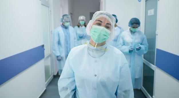 보호 복을 입은 의사 팀. 가면을 쓴 의료진이 현대 병원의 복도를 따라 걸어갑니다.