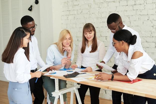 Команда многонациональных людей обсуждает дела в офисе. сотрудники компании общаются, просматривают графики и обсуждают дальнейшую стратегию.