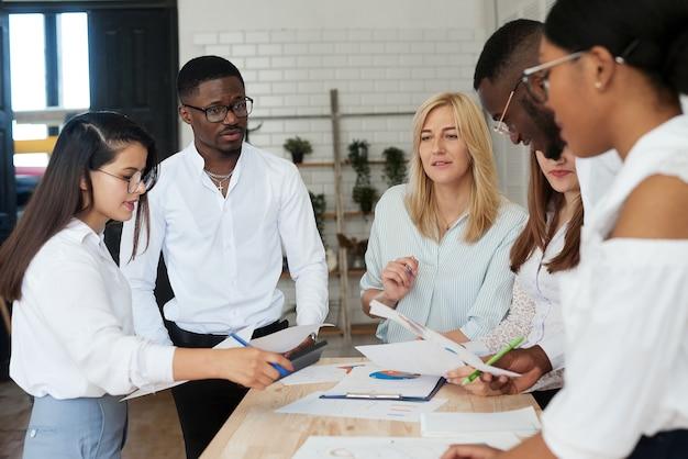 다민족 사람들로 구성된 팀이 사무실에서 비즈니스에 대해 논의하고 있습니다. 회사의 직원은 일정을보고 추가 전략에 대해 논의하면서 의사 소통합니다.