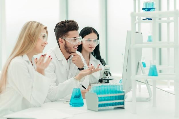 과학자 팀은 컴퓨터를 사용하여 데이터를 확인합니다.