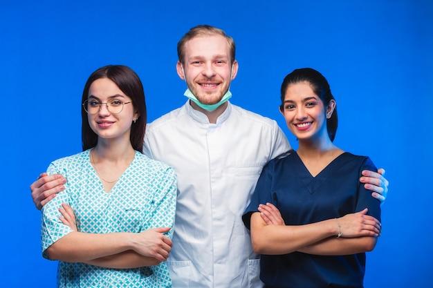 젊은 의사 팀입니다. 다국적 사람들 - 파란색 배경에 의사, 간호사 및 외과 의사. 다른 국적의 의대생들이 감방을 찾고 있습니다.