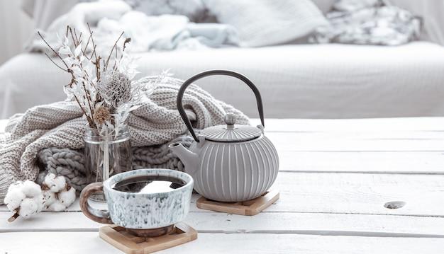 Hygge 스타일의 거실에 찻 주전자와 장식 디테일이있는 아름다운 세라믹 컵이 있습니다. 가정의 편안함과 현대적인 스타일의 개념.