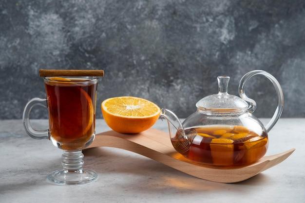 Чайник с чаем и долькой апельсина на деревянной доске.