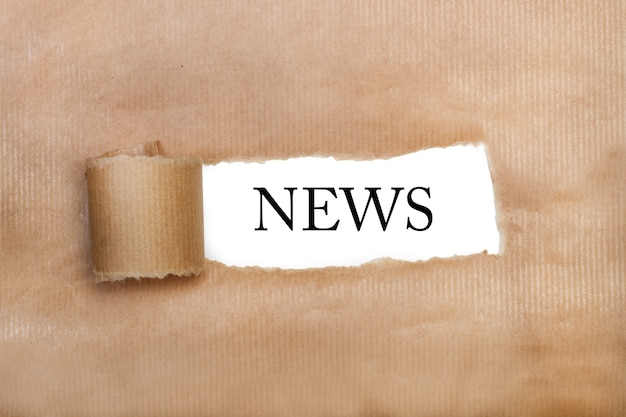 Слеза оберточной бумаги с надписью новостей в ней