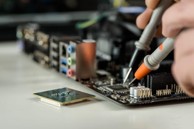 기술자가 컴퓨터 마더보드의 서비스 가능성을 확인합니다.