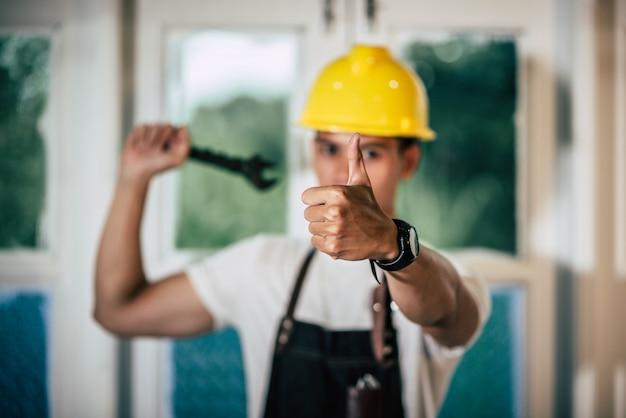 Техник держит отвертку и держит большой палец.
