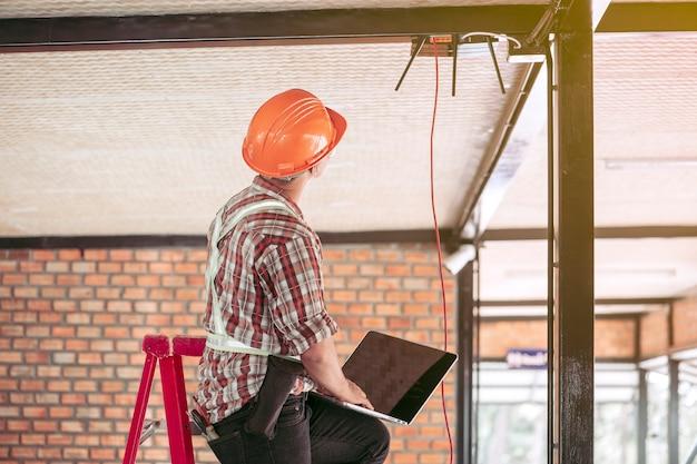 기술자가 건물에 인터넷을 설치 한 후 신호를 확인하고 있습니다.