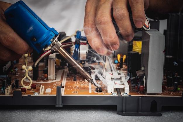 기술자가 납땜 인두와 리드 코일을 사용하여 회로 기판을 수리하고 있습니다.