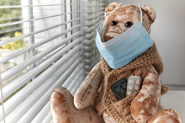의료용 마스크를 쓴 테디베어가 창밖을 슬프게 바라보고 있다. 격리된 아픈 아이