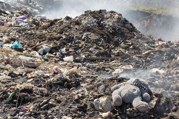 Плюшевый мишка брошен посреди мусорной свалки