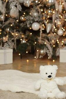 テディベアは、装飾された輝くクリスマスツリーの近くに座っています
