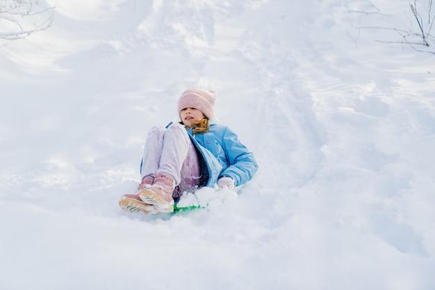 Девушка в розовой шляпе и синем пальто пытается переехать на зеленых санках со снежной горки.
