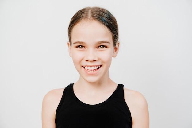 검은 티셔츠에 수집 된 머리카락을 가진 십대 소녀가 서서 치아를 보여주는 미소.