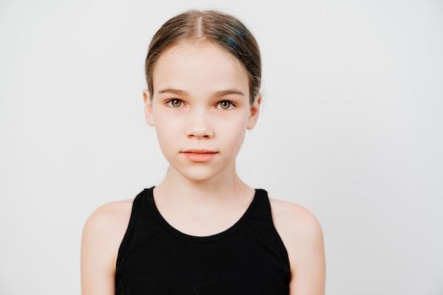 黒のtシャツに髪を集めた10代の少女が白い背景の上に立っています。