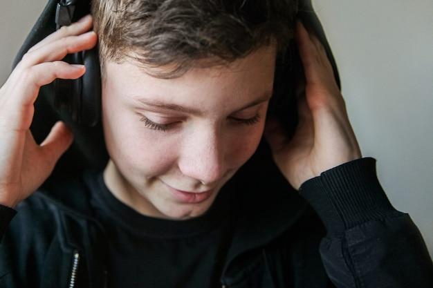 검은 후드와 큰 헤드폰을 입은 십대 소년이 눈을 감고 음악을 듣는다.