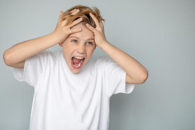 Подросток в повседневной футболке кричит, держась за голову руками с агрессивным выражением лица, из-за проблем подросткового возраста