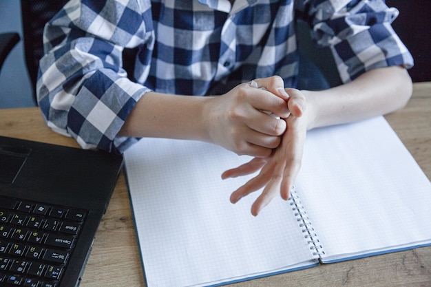 自宅でのトレーニングの過程でチェックシャツを着た10代の少年が、ノートからシートを引き裂き、手にくしゃくしゃにしました。