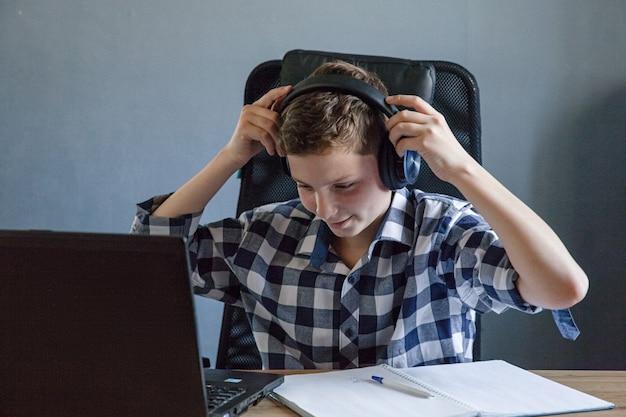 체크 셔츠에 십 대 소년 노트북에 집에서 연구합니다. 그는 열린 노트북을 들고 테이블에 앉아 있습니다. 헤드폰이 노트북에 걸려 있습니다. 원격 학습 주제