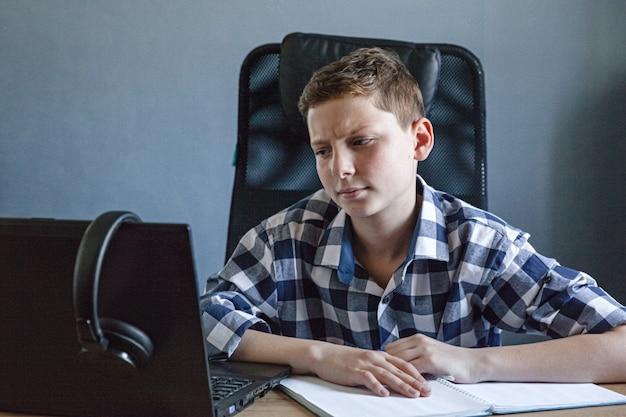 체크 셔츠에 십 대 소년 노트북에 집에서 연구합니다. 그는 열린 노트북을 들고 테이블에 앉아 있습니다.