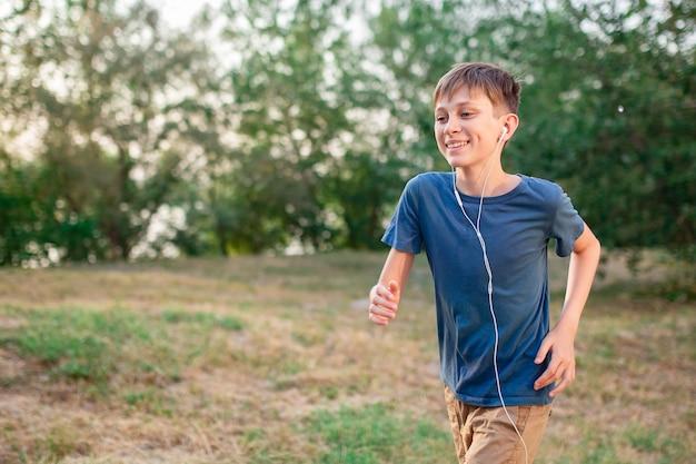 10代の少年は、音楽を聴いているヘッドフォンで自然の中で走っています
