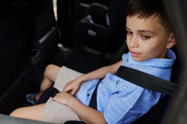 シートベルトを着用した10代の少年は、保護用のチャイルドブースターカーシートで車で移動します。子供と一緒に安全に旅行する。車内でのお子様の安全な移動