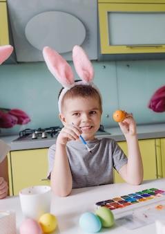 頭にウサギの耳を持った10代の少年は、イースター休暇を見越して水彩絵の具で卵を描きます。家族の伝統
